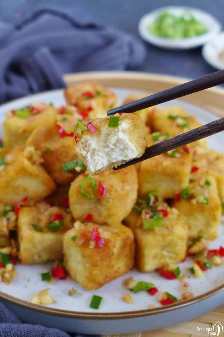 chopsticks picking up a piece of half eaten fried tofu