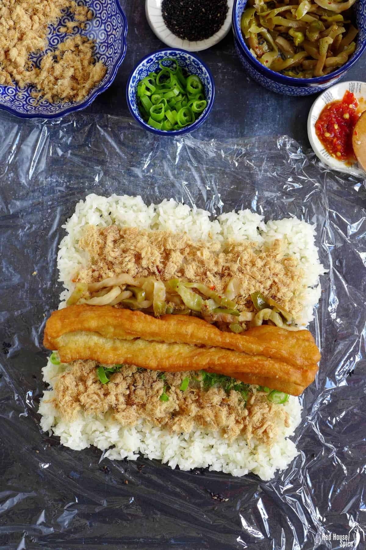A Chinese doughnut stick, pork floss and preserved vegetable over a layer of rice.