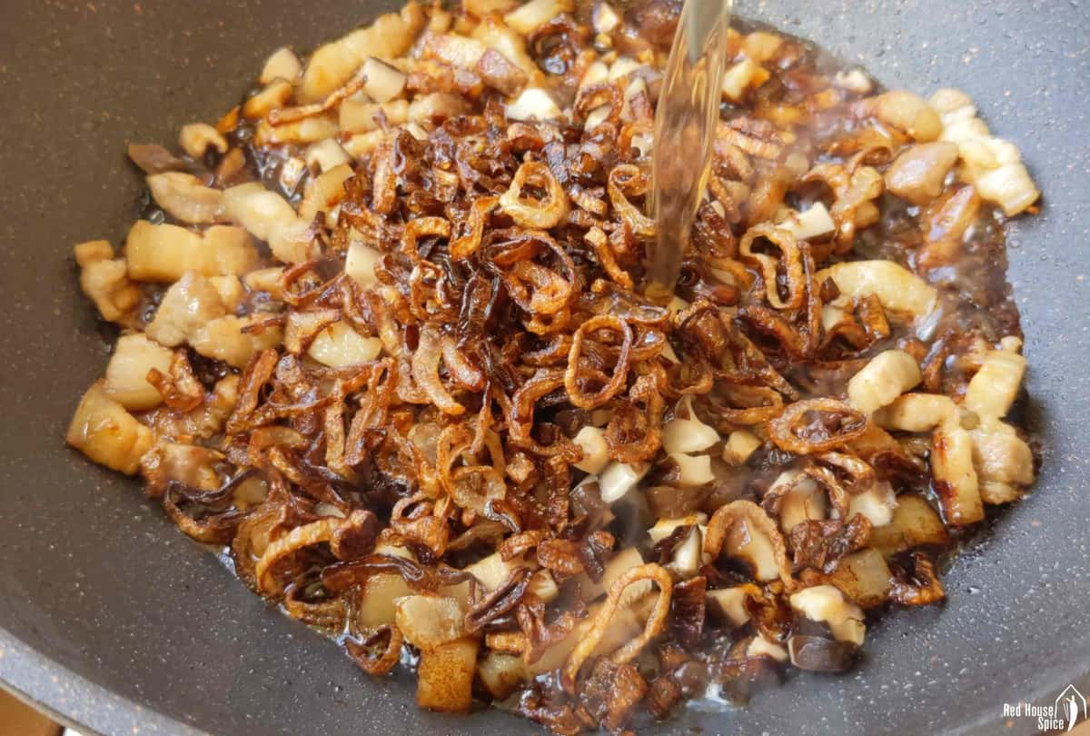 pouring water into a wok with pork and crispy shallots.