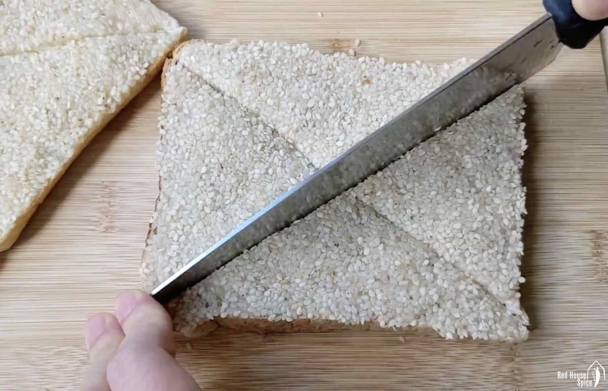 Cutting a piece of uncooked shrimp toast into triangle shaped pieces