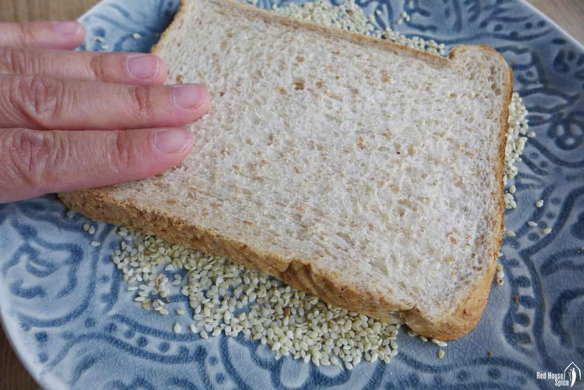 Pressing a piece of toast over sesame seeds.