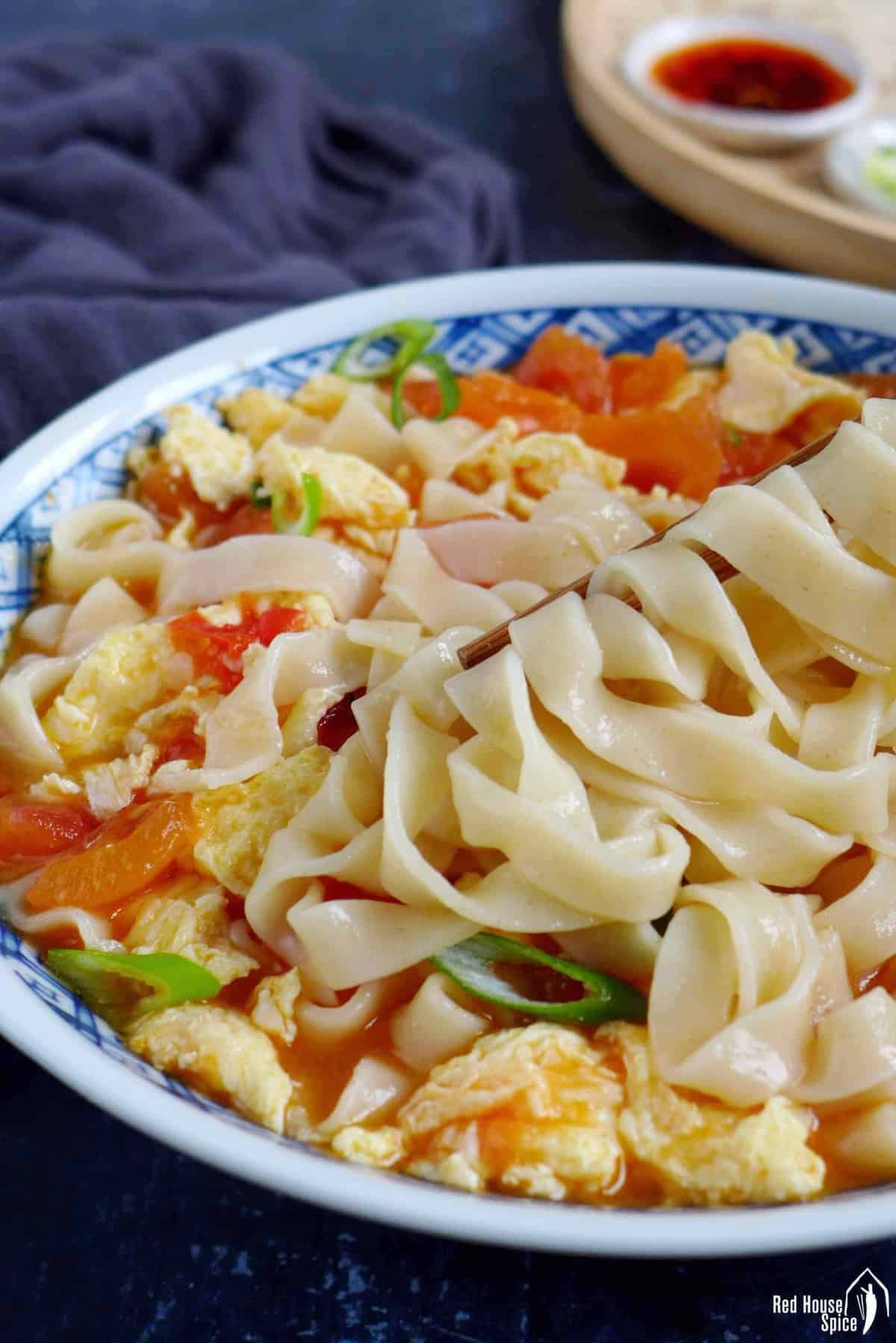 flat noodles held by chopsticks