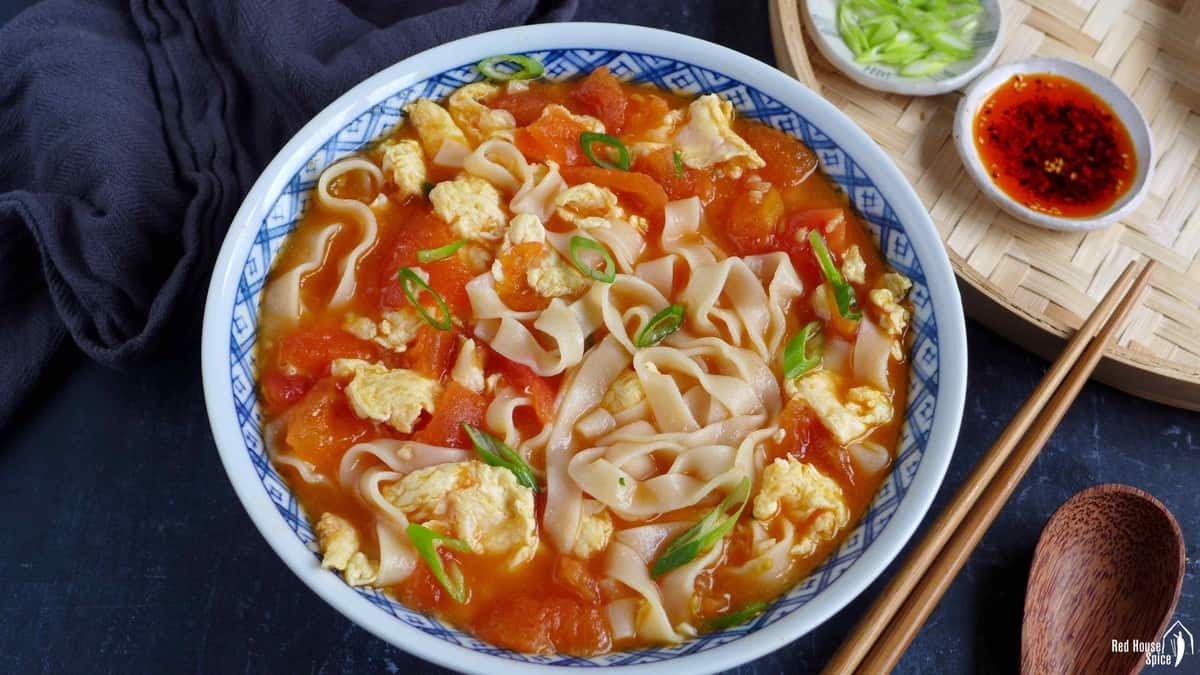 Noodles with tomato and egg soup in a bowl