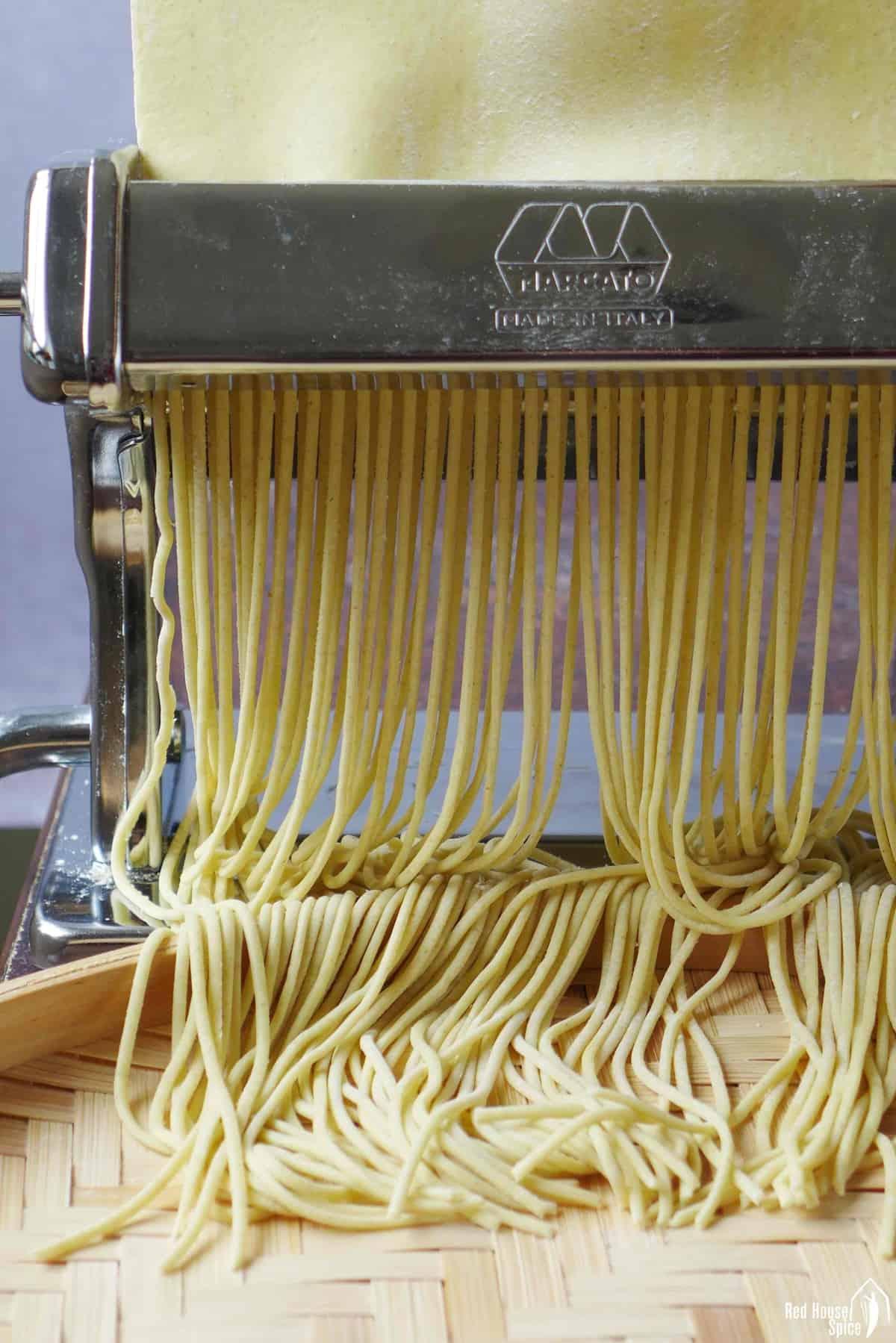 Cutting dough sheet into round noodles through a pasta cutter