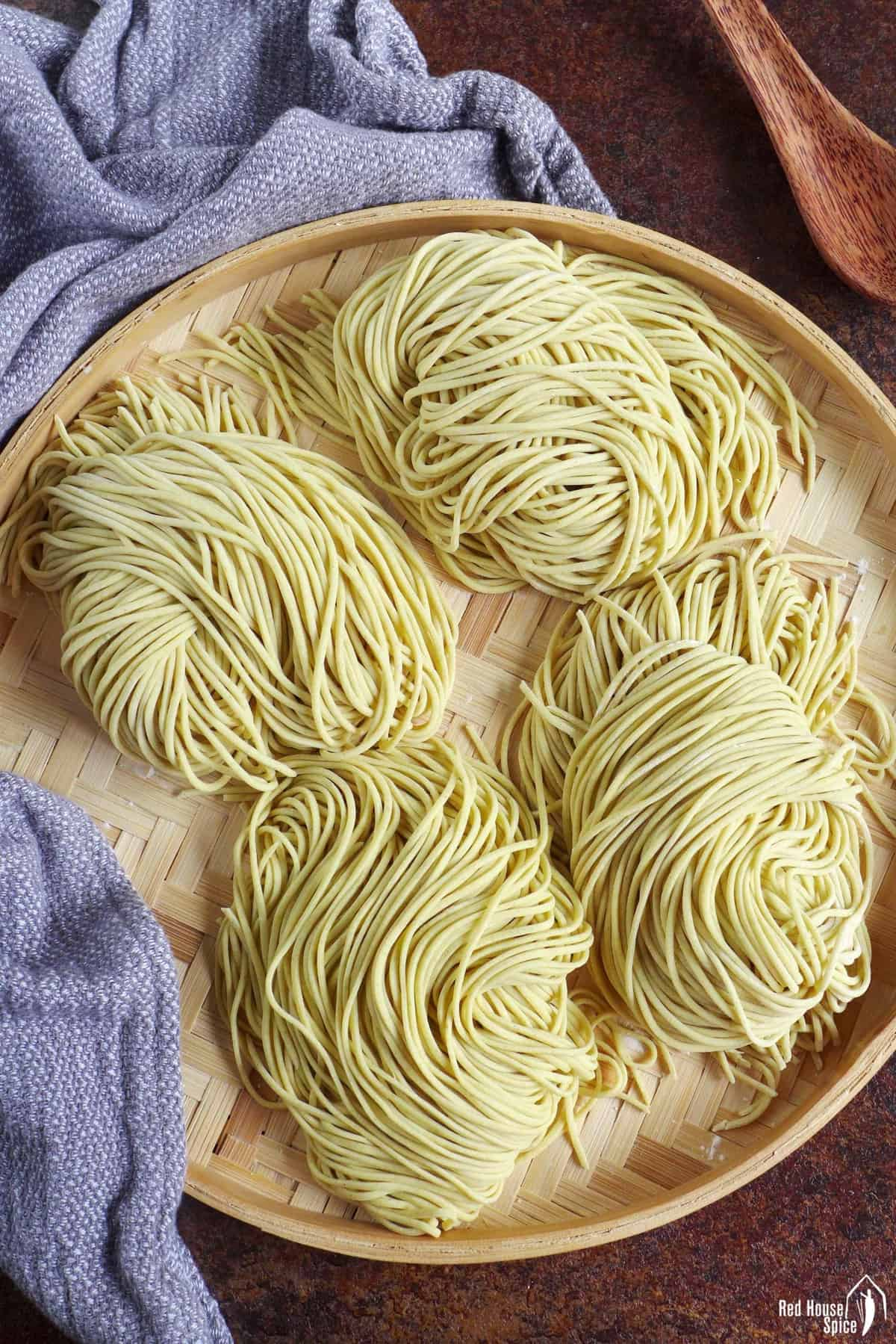 four portions of fresh alkaline noodles on a tray