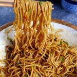 hot dry noodles lifted by chopsticks with overlay text that says hot dry noodles.