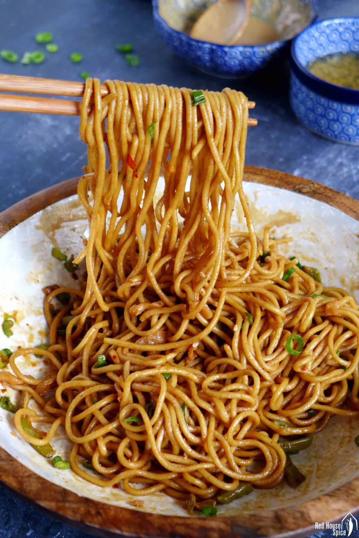 hot dry noodles lifted by chopsticks.