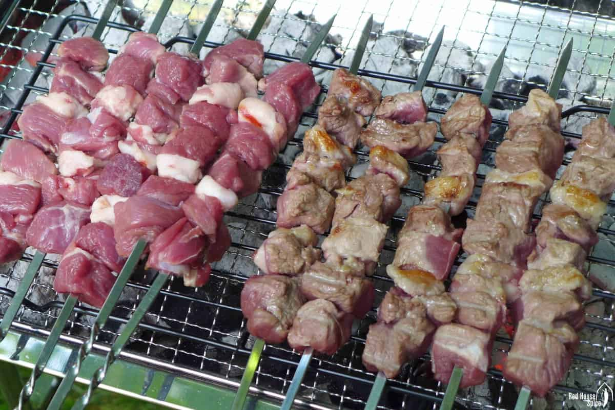 Grilling raw lamb on skewers over charcoal