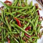 A plate of fried beans with overlay text that says Sichuan green beans.