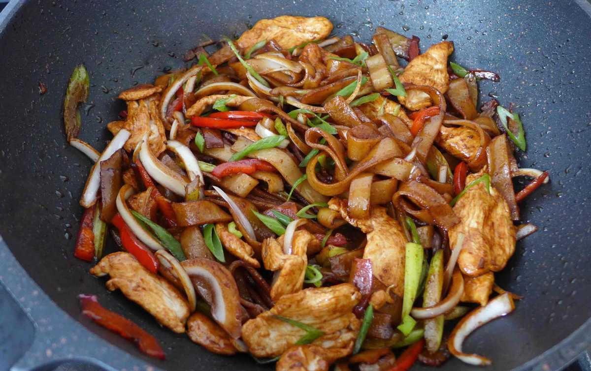 frying chicken, vegetable and rice noodles in a wok.