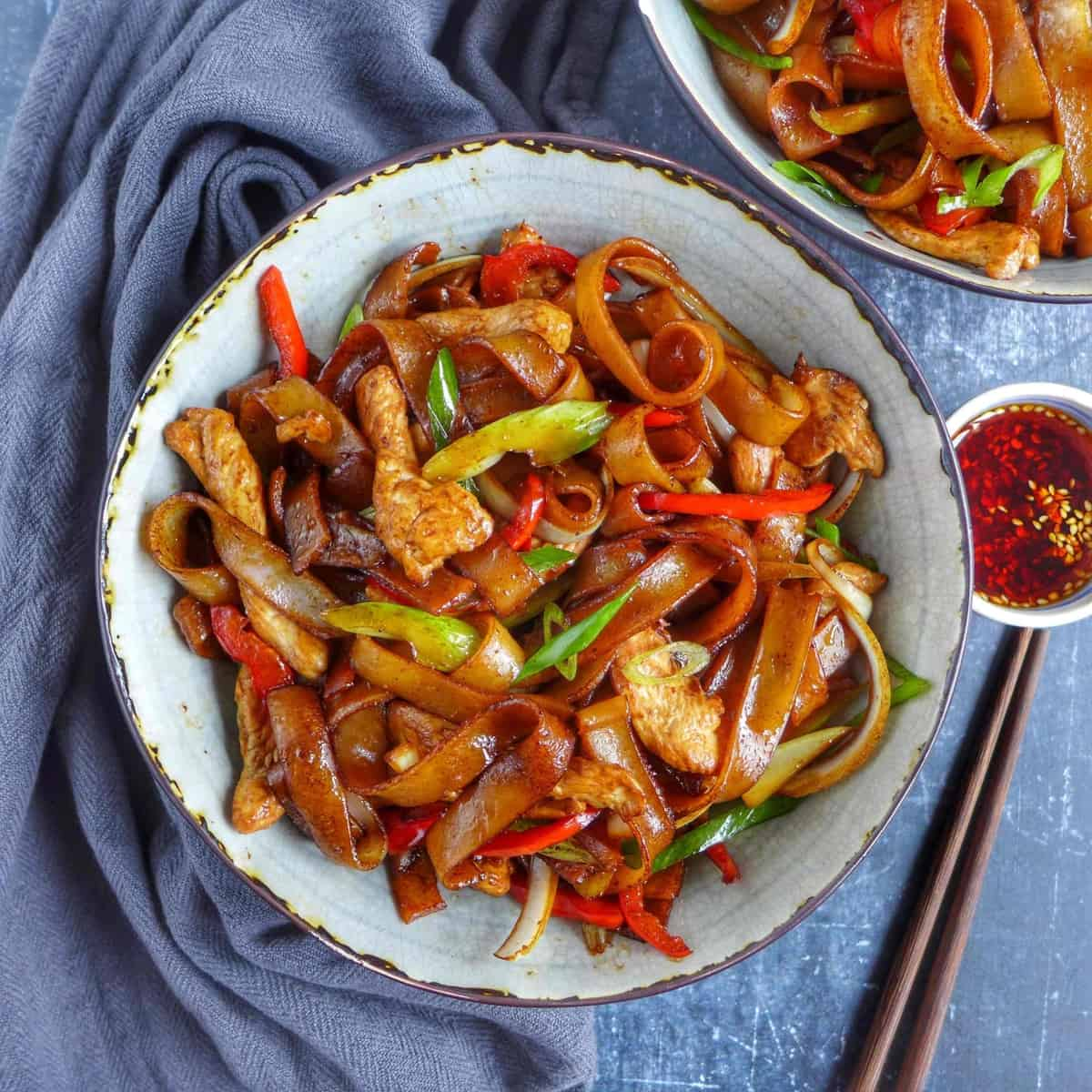 a bowl of chicken chow fun with chili oil on the side.