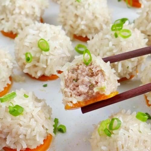 A half pearl meatball held by chopsticks.