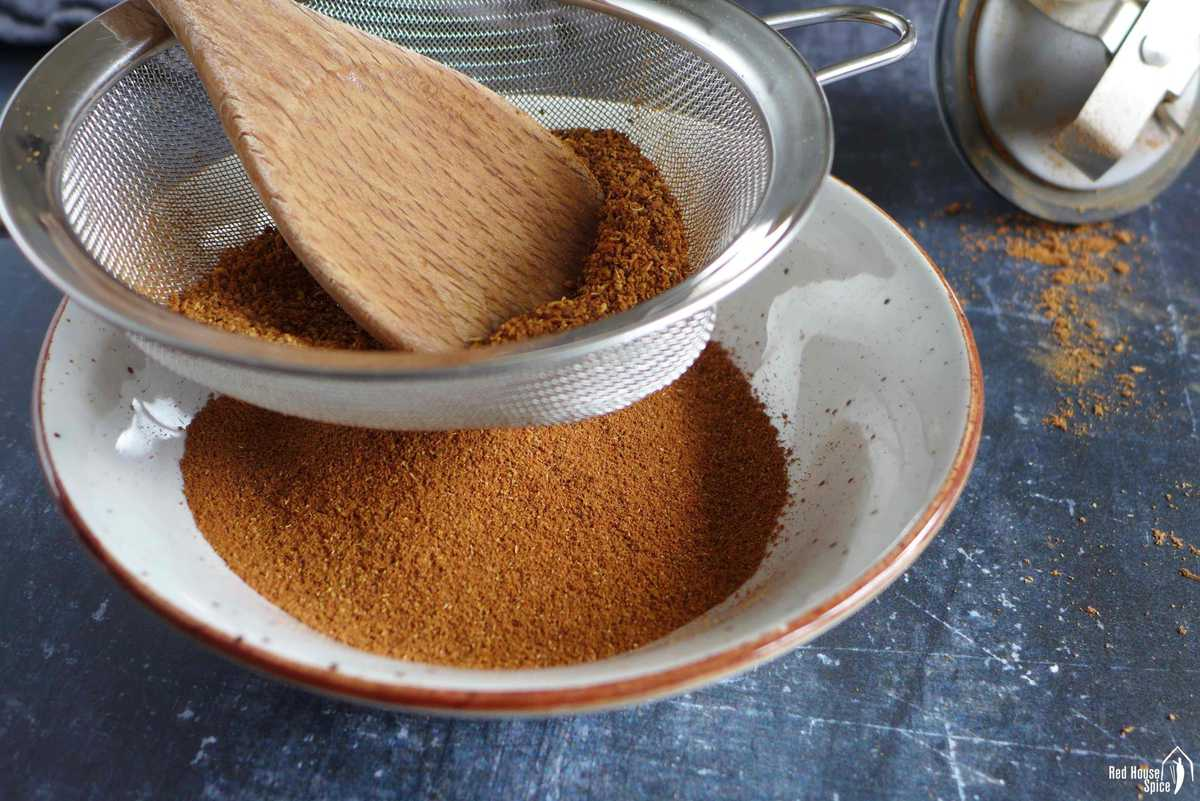Sifting five spice powder through a sieve.